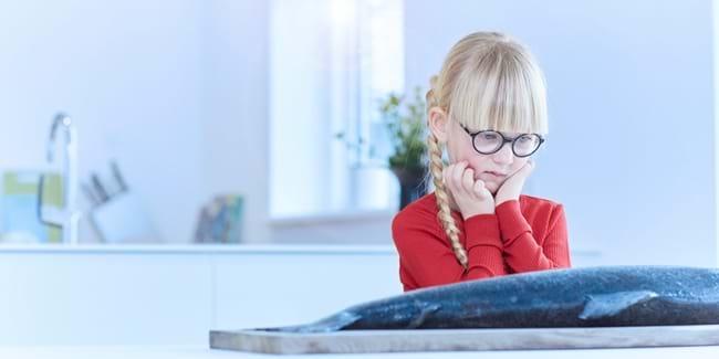 Pige med cerebral parese kigger undrende på laks, der ligger på bordet