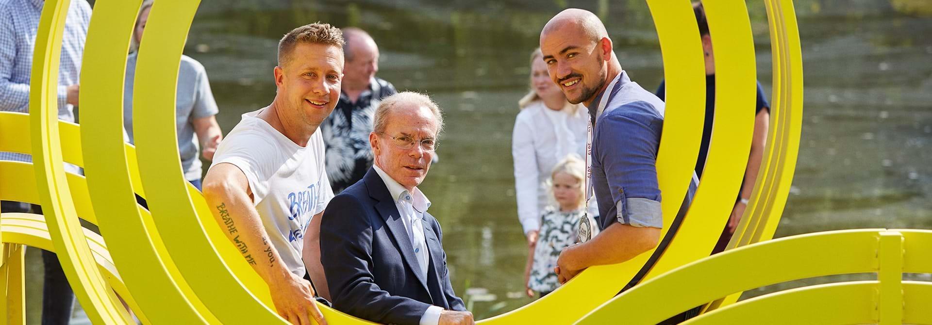 Jeppe Hein, Nick Elsass og Sebastian Frederiksen sidder på en skulptur